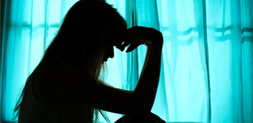 silhouette-of-woman-sitting-in-bed-by-window-picture-id635810582